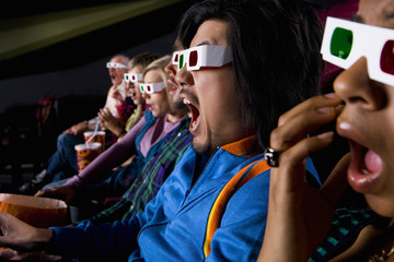 Audience in cinema wearing 3D glasses, close-up