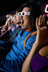 Audience in cinema wearing 3D glasses, making faces, close-up