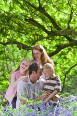 Family posing in field of bluebell flowers