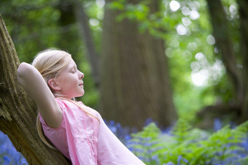 Girl relaxing on tree trunk