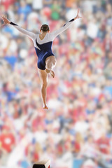 Female gymnast jumping on balance beam