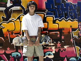 Boy posing in front of graffiti wall