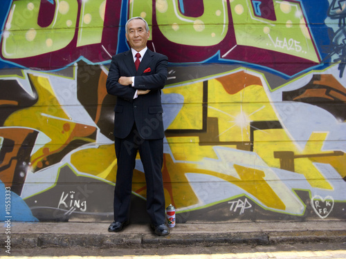 Businessman posing in front of graffiti wall