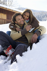 Mixed race couple hugging in winter setting