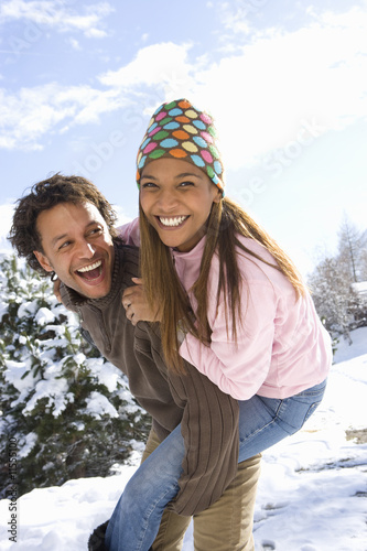 Portrait of happy mixed race couple in snow
