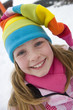Portrait of young girl in multi-colored winter hat