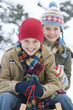 Portrait of young boy and girl sitting on sled