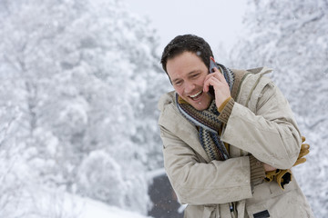 Mid adult man on the phone outdoors in snow