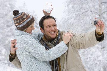 Happy mid adult couple taking photo of each other in snow