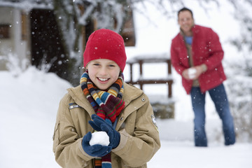 Father and son holding snowballs in snow