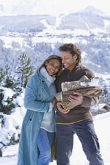 Mixed race couple holding firewood in winter setting
