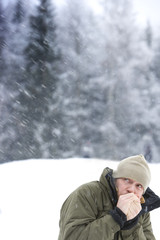 Mid adult man warming hands in snowy weather