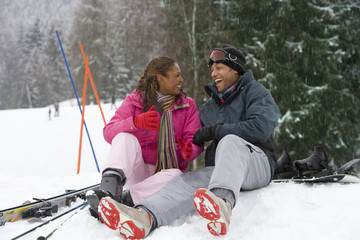 Mixed race couple sitting in snow on ski vacation