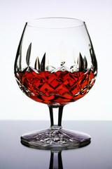 glass of cognac on white background