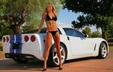 Blond model într-un bikini pozat cu o masina fierbinte.