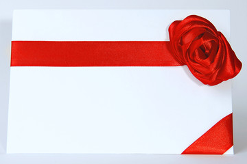 Envelope with red ribbon isolated on white