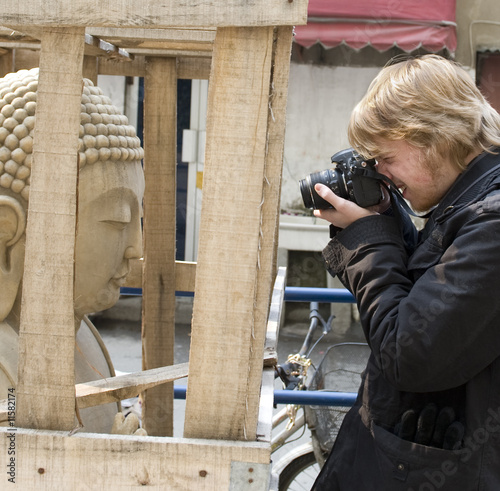 Photographer taking a photo of a Buddha in a box