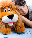 Beautiful sleeping girl with her Plush lion poster