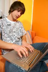 Boy relaxing on sofa in livingroom using laptop for internet