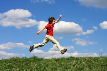Boy running, jumping against blue sky
