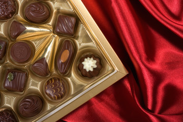 Golden chocolates box on red satin background