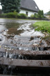 Leinwanddruck Bild - Regenwasser fliesst in Gulli