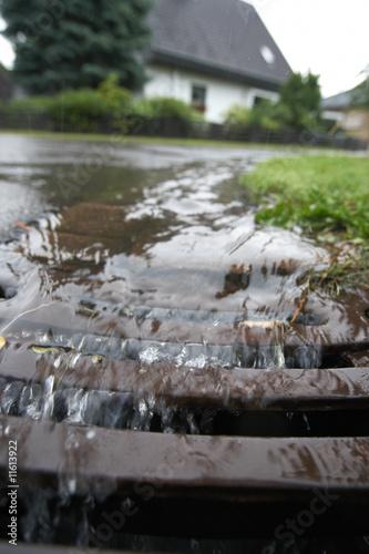 Leinwanddruck Bild Regenwasser fliesst in Gulli
