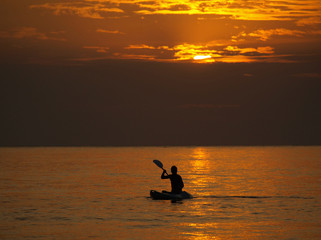 Silhouette of man kayaking at sunset