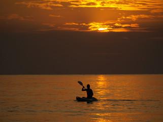 Silhouette of man kayaking at sunset