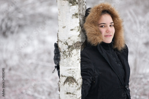 Portrait of a cute girl on a cold winter day near tree