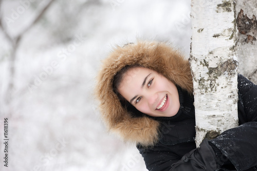 Smiled cute girl on a cold winter day near tree