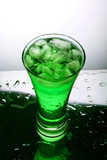 Glass with green beverage and ice poster
