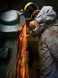 Tradesman at work grinding steel. poster