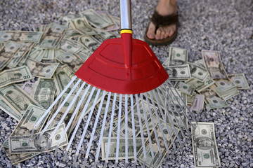 Cleaning black dolar money with rake, metaphor