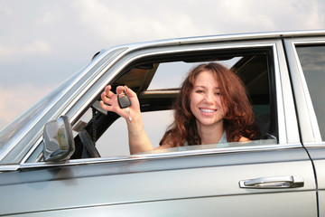 Girl in window of car with  key