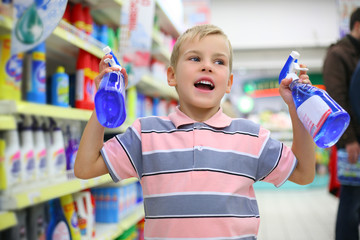 Boy in household chemical goods department in shop