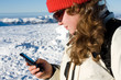 Female skier writing message from her cell phone