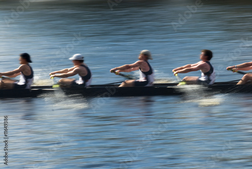 Teamwork, rowers in a rowing boat pulling in harmony