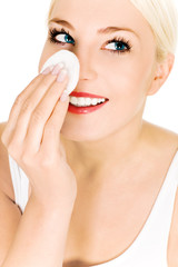 Woman using cotton pad on face