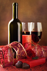 Red wine, candle and chocolate hearts, still life