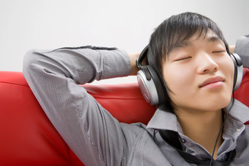 The young man in ear-phones relaxes listening to music