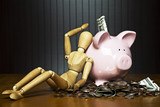Manikin leaning against a piggy bank surrounded by money poster