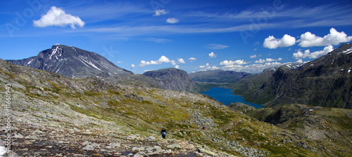 Calm mountain lake landscape with hiker, Jotunheim, Norway