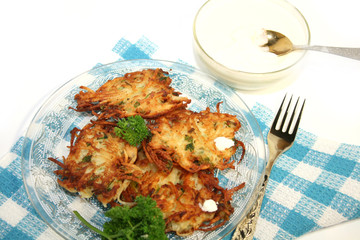 Potato pancakes , served with sour cream. Isolated.