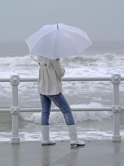 Chica con paraguas mirando al mar