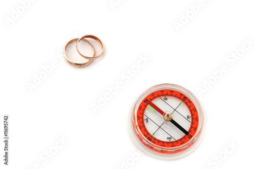 isolated compass with golden wedding rings
