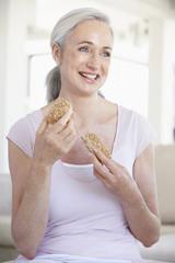Senior Woman Eating Brown Bread Roll