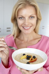 Mid Adult Woman Eating Porridge With Fresh Fruit