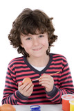 Child adorable adorning Easter eggs poster
