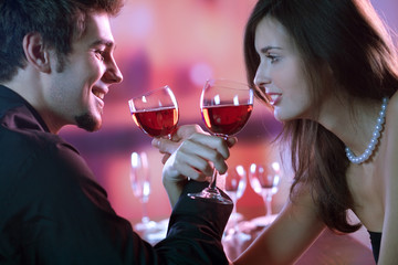 Young couple with glasses of red wine in restaurant
